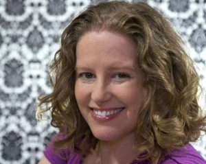 Portrait image of Rachelle Winkle-Wagner wearing a purple shirt in front of a black and white decorated wall.