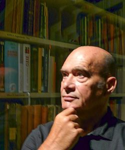 Portrait image of Toma Longinovic holding his chin standing in front of book shelves with a glass reflection in front of the shelves.