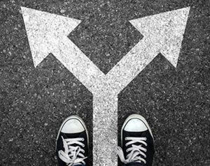 Image of two identical arrows pointing in different directions painted in white on black asphalt and two shoes a the base of the arrows.