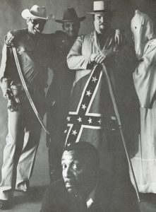 Black and white satirical image of Dick Gregory (a frowning Gregory appears in the bottom foreground of the image while a smiling group of men appear standing in the upper background, including a police officer, a hooded Klansman, a confederate civil war soldier holding a bayonet, and a man holding a confederate flag).