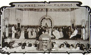 """Black and white image with graphic frame depicting performers on a stage performing the zaruela """"Filipinas para los Filipinos,"""" which premiered in Manila in 1905."""