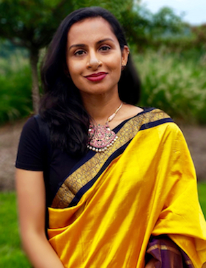 Portrait image of Vijayanka Nair wearing yellow and standing outdoors.