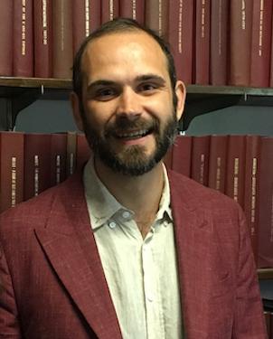 Portrait image of Carmine Grimaldi wearing a burgundy blazer standing in front of book shelves.