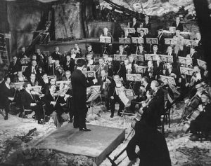 Black and White photo of Sergiu Celibidache conducting Beethoven's Egmont overture in the ruins of the Philharmonie concert hall, musicians are wearing tuxedos and rubble is visible near conductor's podium