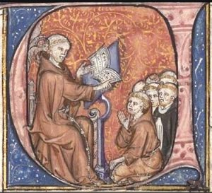 Image of an illuminated initial from a medieval manuscript representing the medieval thinker, John Duns Scotus, sitting at a lectern and lecturing to a group of friars squatting in front of him. A little angel is whispering in Duns Scotus's right ear.