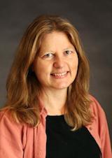 Portrait image of Celia Applegate wearing a salmon-colored shirt.