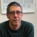 Portrait image of Steven Nadler wearing a dark green sweater seated in front of a poster