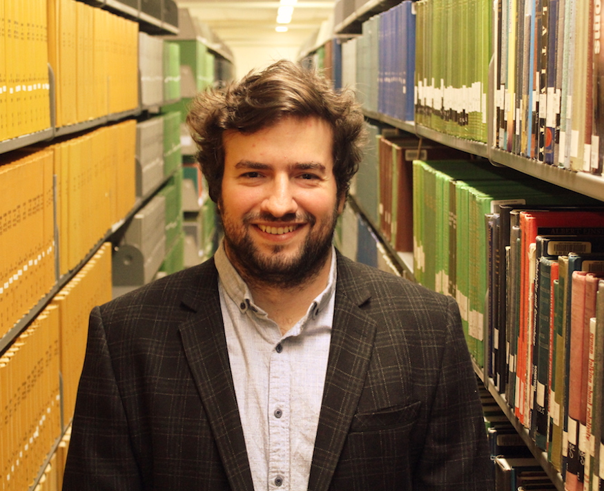 Portrait photo of Ari Sekeryan in a library aisle surrounded by book shelves.
