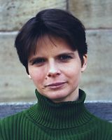 Portrait image of Esther Bauer in front of a stone wall wearing a green sweater