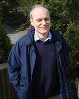 Portrait image of Max Harris standing outdoors wearing a dark blue sweater and windbreaker.