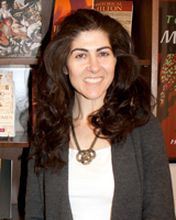 Portrait image of Stacy S. Klein standing in front of book shelves wearing a white shirt, grey sweater, and large necklace