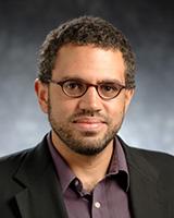 Portrait image of Vincent Lloyd wearing glasses, a purple shirt, and a black jacket