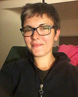 Portrait image of Sara Trevisan seated wearing glasses and a black sweatshirt
