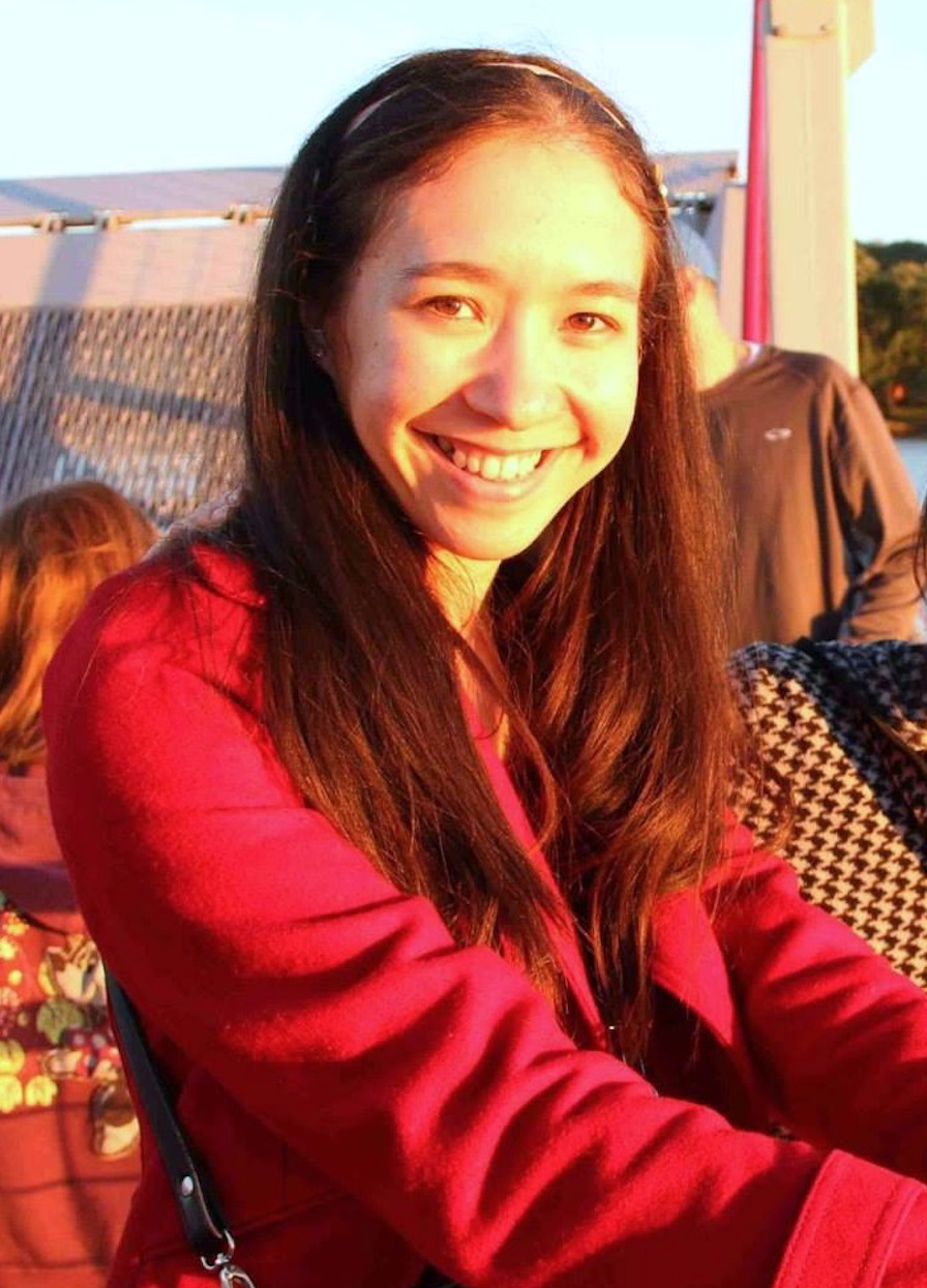 Portrait image of Erica Kalnay: Smiling multiracial Asian/white woman with long black hair wearing a red coat.