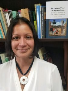 Portrait image of Nandini Pandey wearing a white shirt and a large necklace standing in front of book shelves with her book displayed on the top shelf