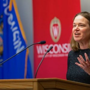 Image of Anna Andrzejewski speaking at a podium with two microphones in front of a Wisconsin state flag and a University of Wisconsin banner. She is wearing a grey shirt and gestures with her left hand