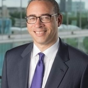 Portrait image of Jonathan Holloway wearing a grey suit, glasses, and purple tie standing in front of a mirror