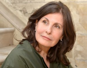 Portrait image of Alice Kaplan seated in front of stone steps wearing a green shirt looking over her right shoulder. She wears her shoulder-length brown hair down