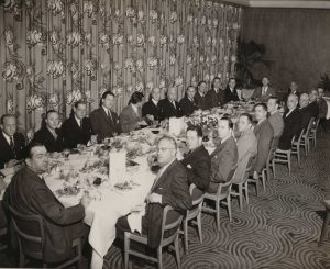 Black and White image of a long table with many men in suits seated around the table, looking at the camera