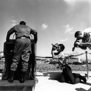 black and white image of the back of Fidel Castro speaking at a podium with men holding news cameras kneeling at the right side of the image