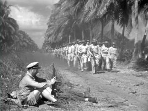 """This image is a black and white frame still from the film """"They Were Expendable."""" On the left, it shows two tired officers resting by the side of a road. On the right, a platoon of soldiers marches down the road in two rows toward the camera flanked by a row of palm trees."""
