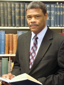 Portrait image of William Chester Jordan wearing a suit and tie standing in front of shelves of books holding an open book but looking at the camera