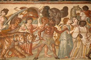 Image of a 3rd-century mosaic depicting a procession of men, women, and animals (including tigers, an elephant, and a giraffe) with a cloven and horned man holding the tigers and a black woman by chains.