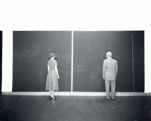 black and white photograph image of a man and woman in 1950s dress standing in front of large single-tone painted canvases with their backs to the photographer