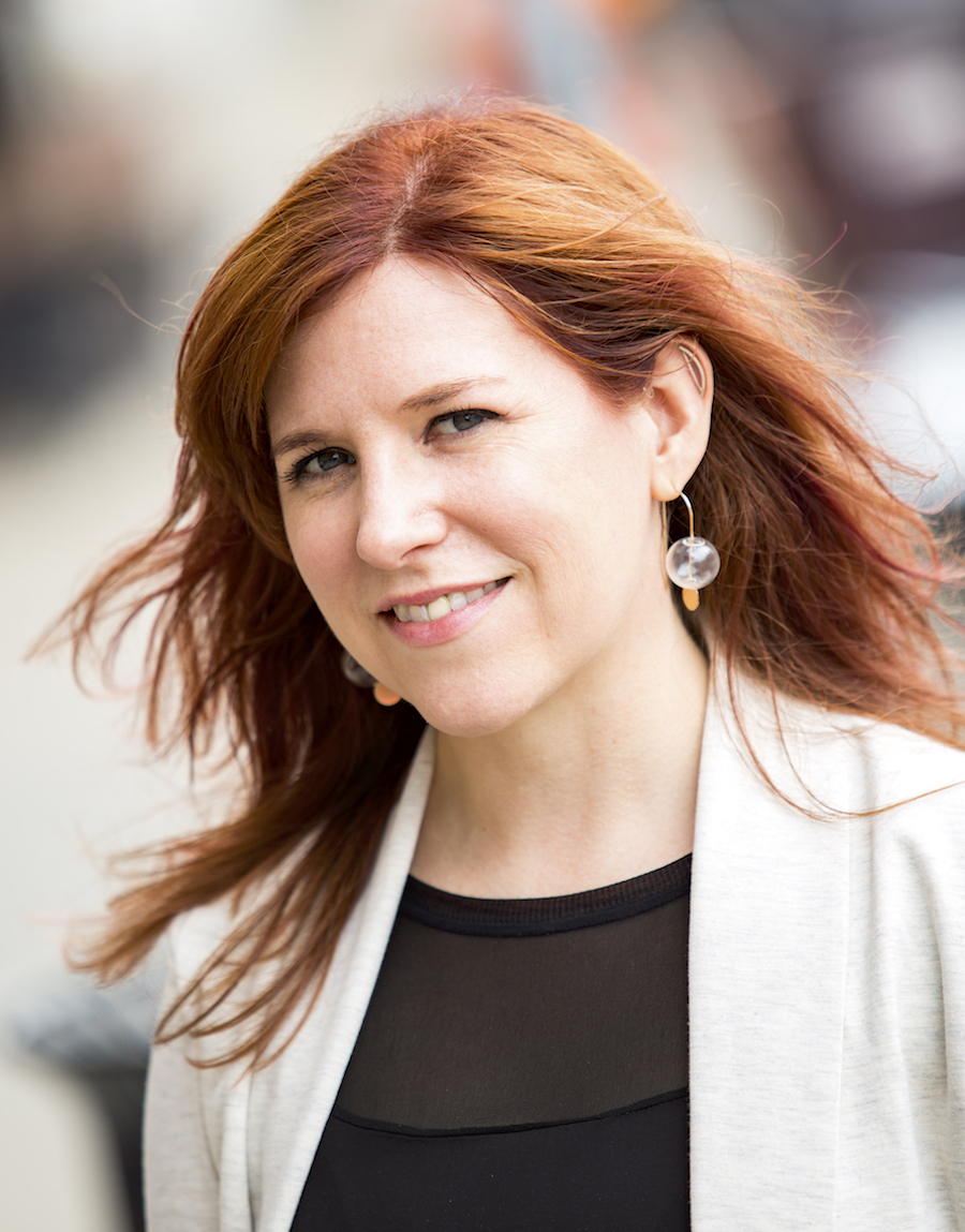 Portrait image of Jocelyn Szczepaniak-Gillece wearing a black shirt and ivory blazer with her long red hair blown back by the wind wearing large glass earrings