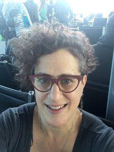 photo portrait or selfie of Rachel Ida Buff wearing dark red glasses and a dark grey/black shirt looking up at the camera