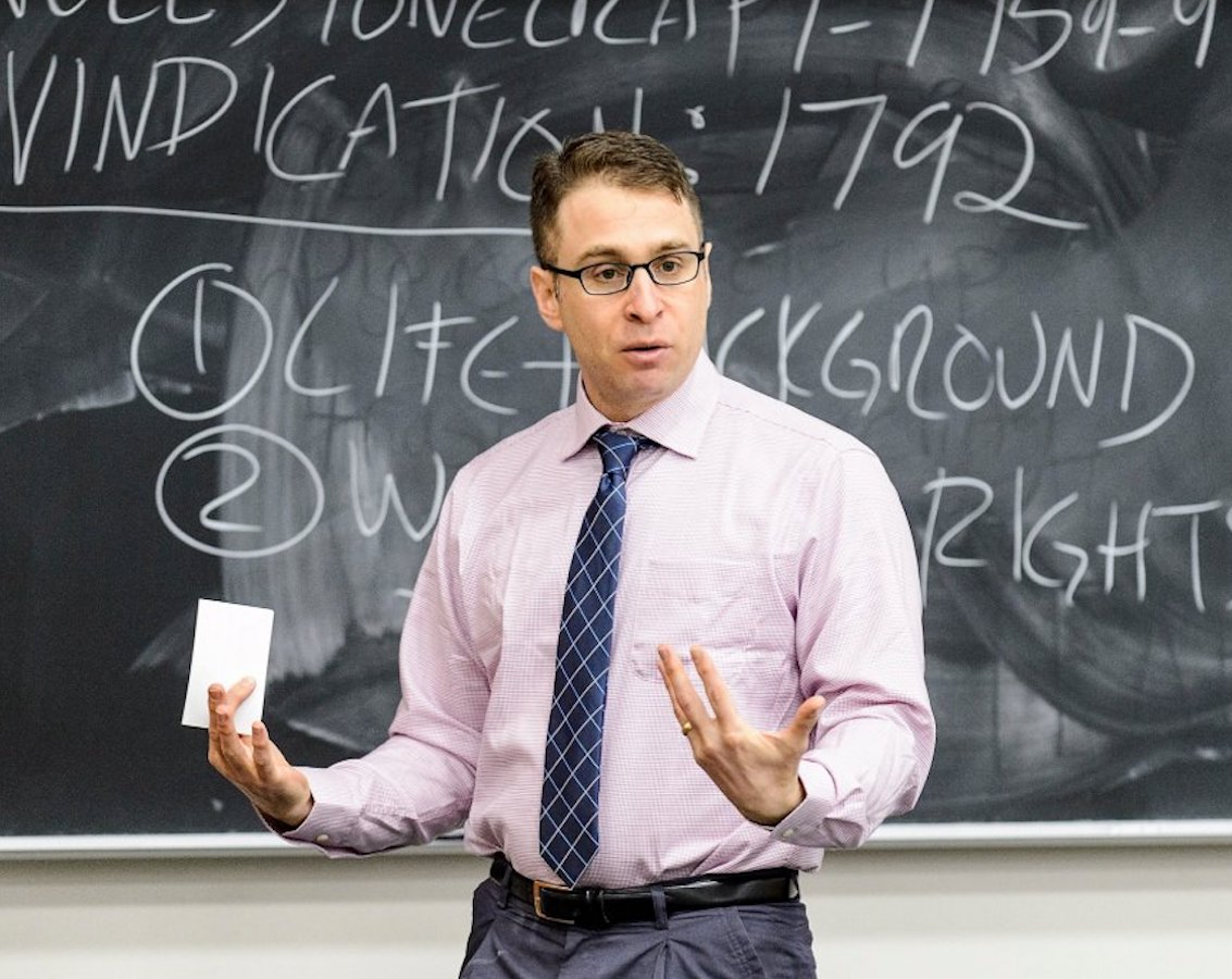 Portrait image of Daniel Kapust standing in front of a filled chalkboard holding an index card speaking to a class. He wears a pink shirt, blue tie, and dark glasses.