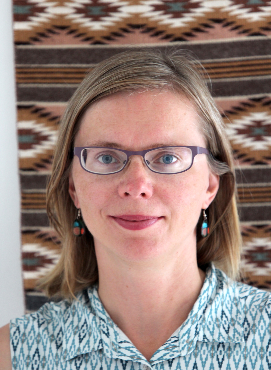 Portrait image of Elizabeth Lapina standing in front of a brown native-patterned woven blanket wearing glasses, dangling earrings, and a turquoise shirt