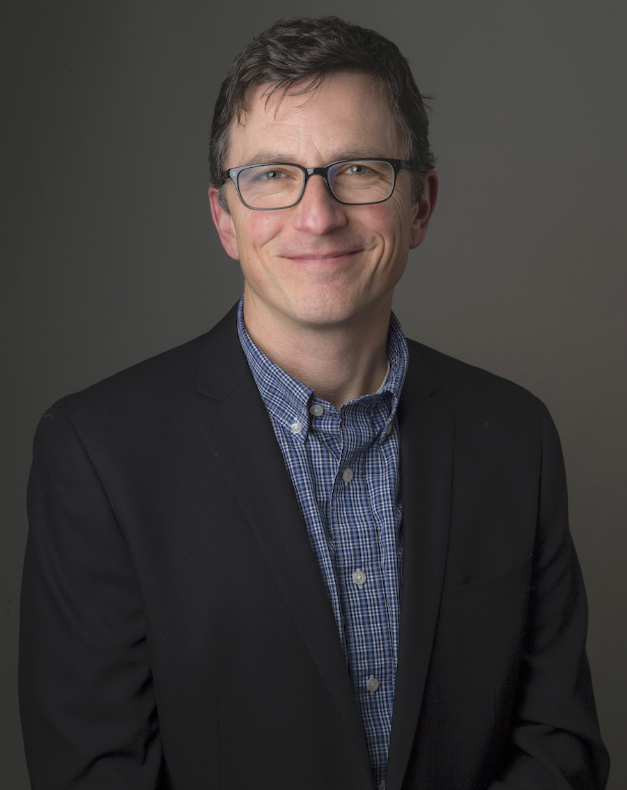 Portrait image of John McGuigan wearing a blue shirt, black jacket, and glasses