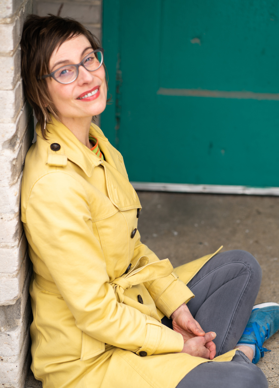 portrait photograph of Annie Menzel: A white woman with short brown hair and blue eyes, gray glasses, silver earrings, and red lipstick, wearing a yellow trench coat with a bit of orange and green striped shirt showing, gray jeans, and blue sneakers, is smiling and sitting cross-legged leaning against a white-painted brick wall in an external entryway. A turquoise door with peeling paint is in the background.