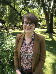 Portrait image of Rebecca Moorman standing outdoors in front of trees. Moorman has short hair, is smiling, and wears a patterned blouse under a brown jacket and dark glasses