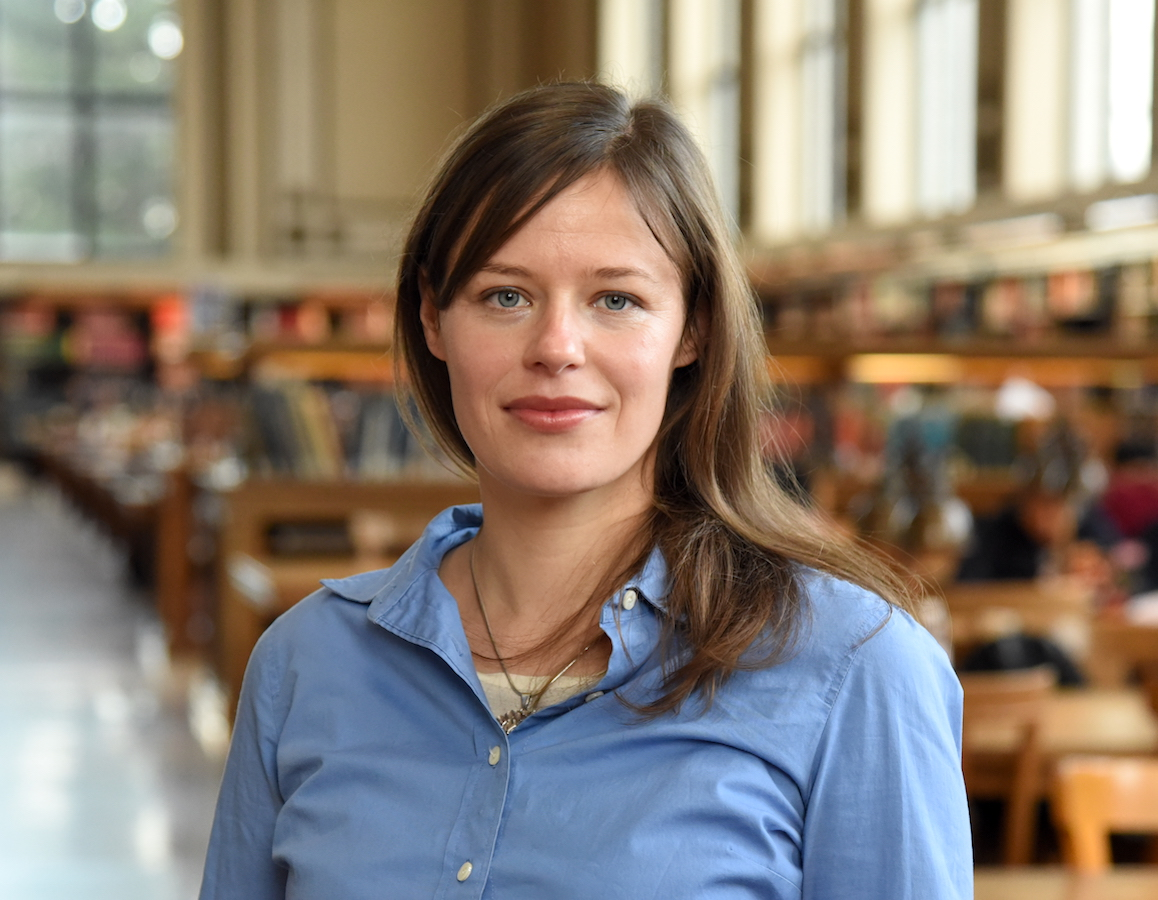 Portrait image of Mirjam Voerkelius standing in a library with tall windows wearing a blue shirt and her hair long around her shoulders