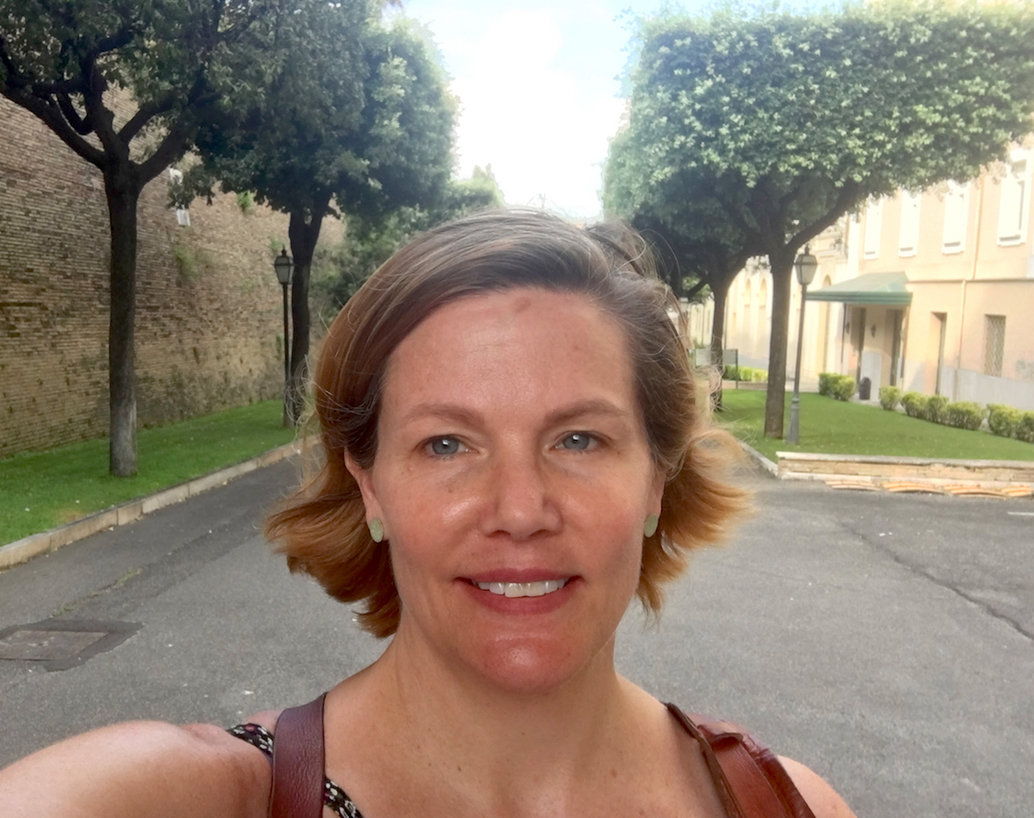 "Portrait image ""selfie"" of Justine Walden standing in a tree-lined street wearing green earrings and leather straps around her shoulders"
