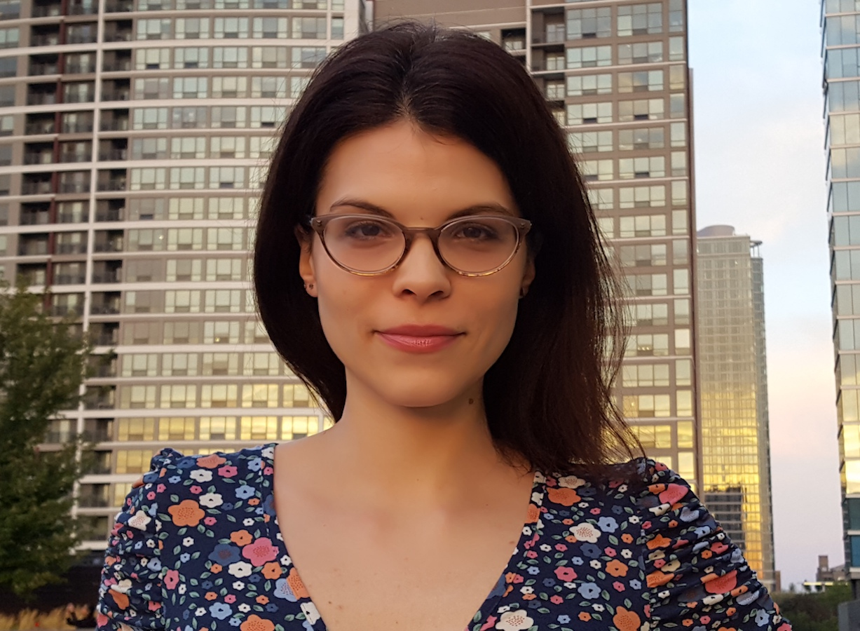 Photograph portrait of Sarah Ann Wells standing outside among tall glass buildings wearing a floral dress, glasses, and her dark brown hair behind her shoulders