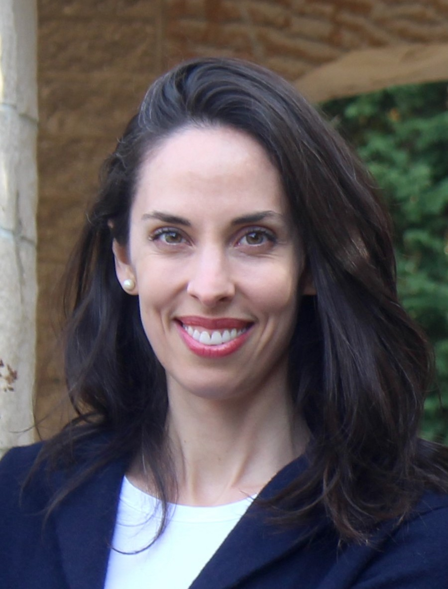Portrait image of Gloria Whiting standing in front of a brick archway wearing a navy blazer and white shirt. Whiting is smiling and wears long dark hair around her shoulders