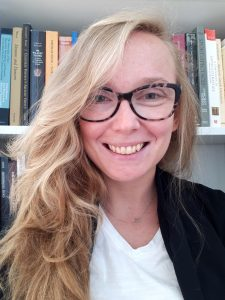 Portrait image of Hanna Golab in front of grey bookshelves wearing a white shirt, black jacket, and black glasses withe her long blonde hair pushed to one side