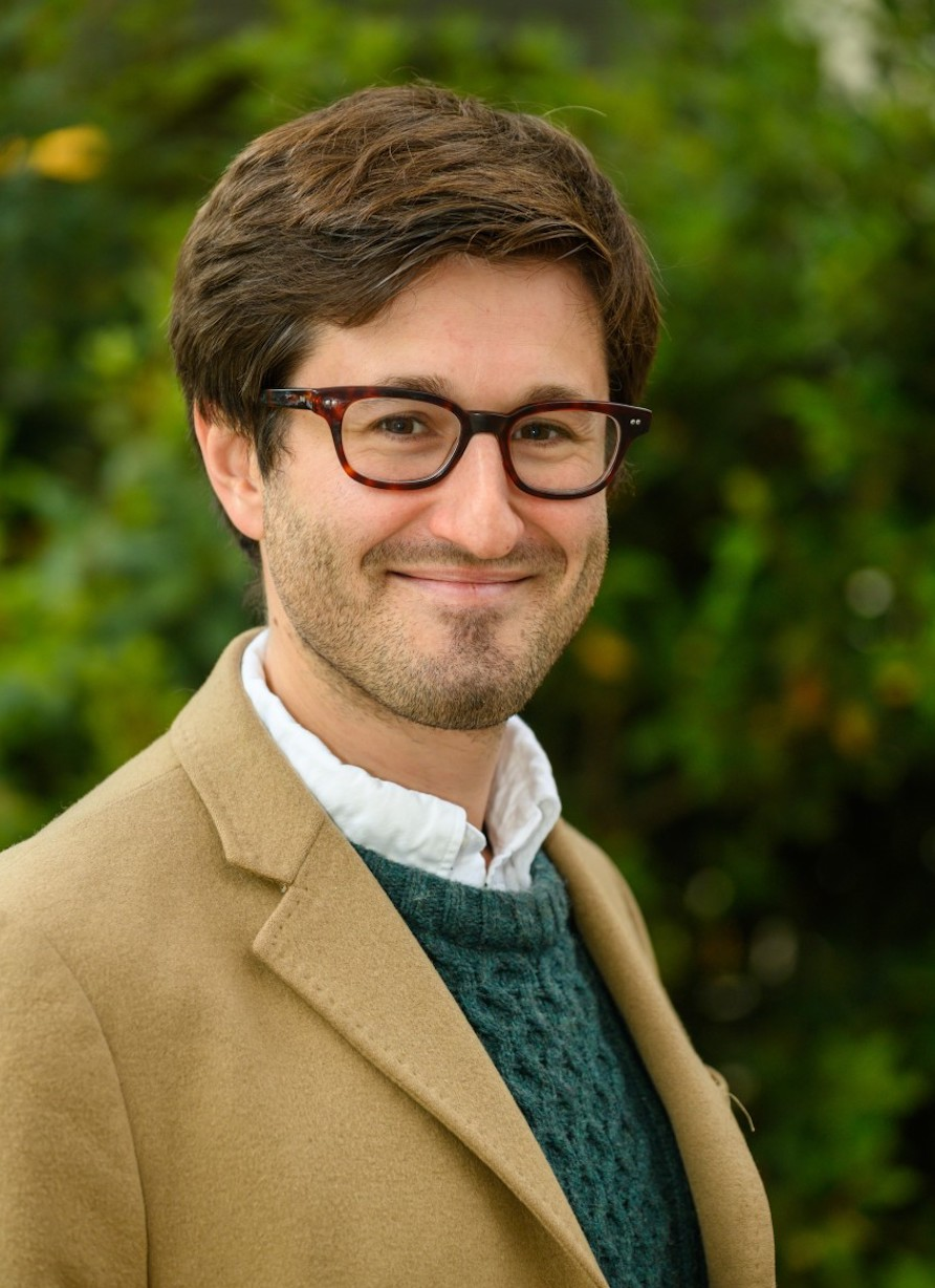 Portrait image of Alexander Statman standing outside in front of lush greenery wearing a camel-colored jacket, green sweater, and brown glasses smiling