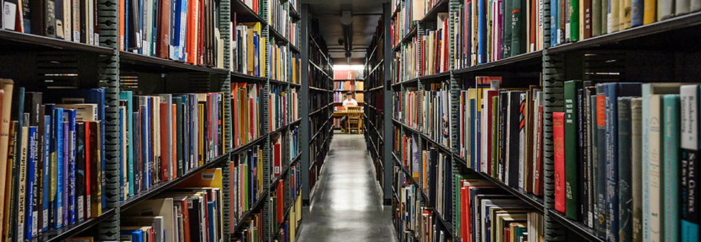 Image of interior of memorial library stacks with dark grey shelves and colorful books stretching into the distance with sharp perspective.