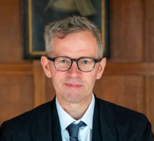 Portrait image of Tim Whitmarsh standing in front of a wood paneled wall wearing dark glasses and a dark blue suit and tie
