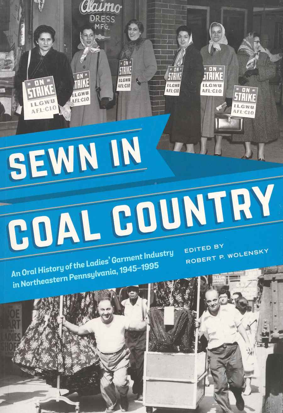 "Image of cover of book ""Sewn in Coal Country"" showing a blue ribbon with title text atop two black and white images: one of women on strike in front of Alaimo Dress shop c. 1953 and one of men pulling loaded garment racks down a New York City street in 1955"