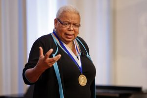 Image of Frances Smith Foster speaking to crowd and gesturing. She wears a black shirt and a medal around her neck.