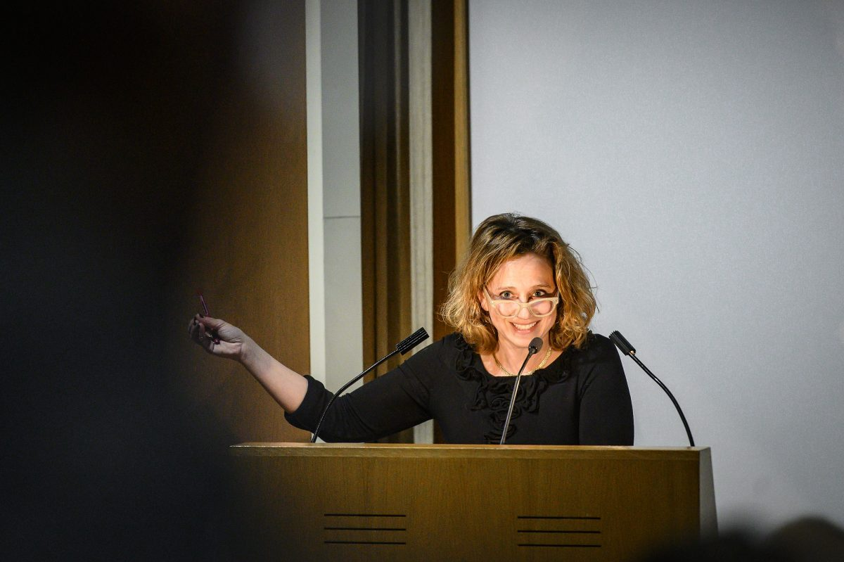 Photograph of a woman at a podium wearing a black shirt and glasses leaning over to speak into a microphone and pointing to the left (speaker's right)