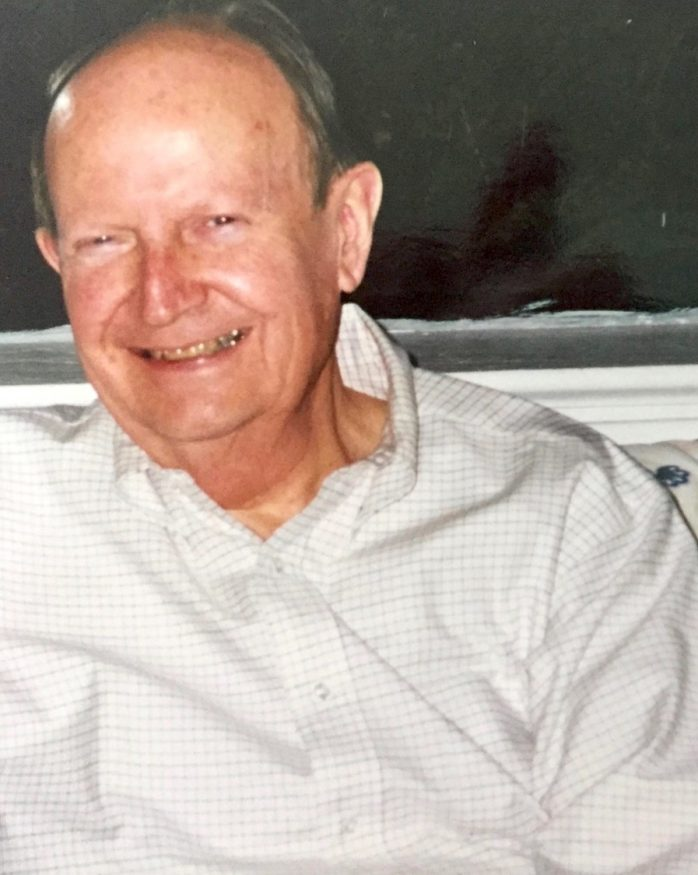 Photograph portrait of a seated man wearing a white and grey checkered shirt, smiling