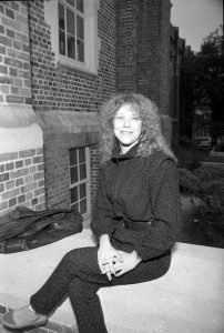Black and white image of woman seated outside brick facade wearing dark closed with her legs crossed and her hands clasped.