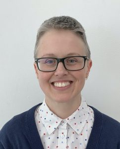 White woman with black glasses and very short brown and gray hair smiling at the camera and wearing a blue cardigan and white collared shirt with polka dots against a white background.