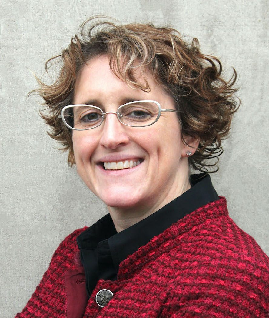 Photograph image of a woman standing against a wall with short hair and glasses smiling and wearing a red jacket